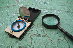 Map, compass and magnifying glass Stock Images