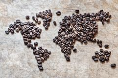 Map of continents from coffee beans on a wooden background. Map of continents from coffee beans on an old wooden background royalty free stock photo