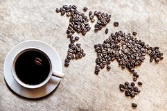 Map of continents from coffee beans on a wooden background. Map of continents from coffee beans on an old wooden background stock photo