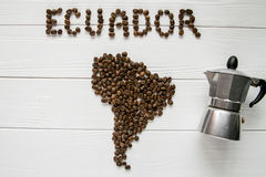 Map of the Ecuador made of roasted coffee beans laying on white wooden textured background with coffee maker. And space for text Stock Images