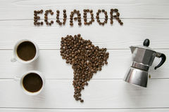 Map of the Ecuador made of roasted coffee beans laying on white wooden textured background with cups of of coffee, coffee maker. Map of the Ecuador made of Royalty Free Stock Photo