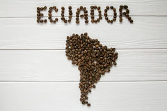 Map of the Ecuador made of roasted coffee beans laying on white wooden textured background. And space for text Royalty Free Stock Photos