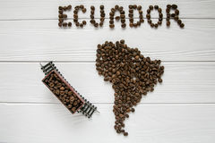 Map of the Ecuador made of roasted coffee beans laying on white wooden textured background with toy train. And space for text Royalty Free Stock Photo