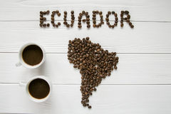 Map of the Ecuador made of roasted coffee beans laying on white wooden textured background with two cups of coffee. And space for text Royalty Free Stock Photography