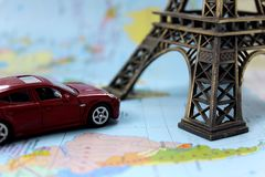 On the map is a toy car and the Eiffel Tower stock photos