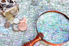 Map of England, vintage magnifying glass and small purse. With English coins royalty free stock images