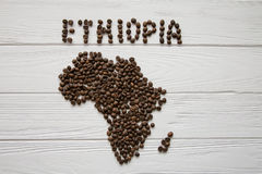 Map of the Ethiopia made of roasted coffee beans laying on white wooden textured background. And space for text Royalty Free Stock Photo