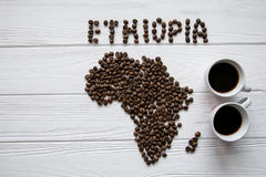 Map of the Ethiopia made of roasted coffee beans laying on white wooden textured background with two coffee cups. Map of the Ethiopia made of roasted coffee Stock Photography