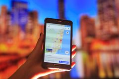 Map of Florida on the phone in the background of a night city. Close Up Of Woman Hand Holding Mobile Phone. Close Up Of Woman Hand Holding Mobile Phone. map of stock photo