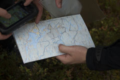 Navigating Map GPS. A map and GPS are being held in hands Royalty Free Stock Photography