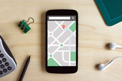 Map gps navigation application on smart phone screen on wooden d Stock Photos