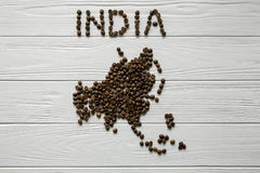 Map of the India made of roasted coffee bean Map of the Asia made of roasted coffee bes laying on white wooden textured background. Map of the India made of Stock Photos