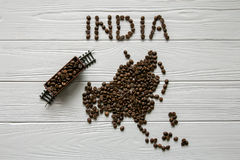 Map of the India made of roasted coffee bean Map of the Asia made of roasted coffee bes laying on white wooden textured background. Map of the India made of Royalty Free Stock Photo