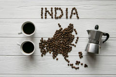 Map of the India made of roasted coffee beans laying on white wooden textured background Royalty Free Stock Photo