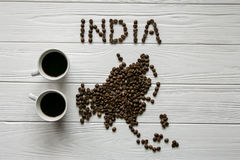 Map of the India made of roasted coffee beans laying on white wooden textured background with two cups of coffee. Map of the India made of roasted coffee beans Stock Photo