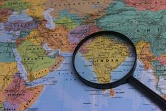 Map of India through magnifying glass on a world map. India map through magnifying glass on a world map Royalty Free Stock Photography