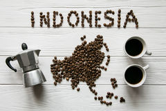 Map of the Indonesia made of roasted coffee beans laying on white wooden textured background with cups of coffee and coffee maker. Space for text Royalty Free Stock Images