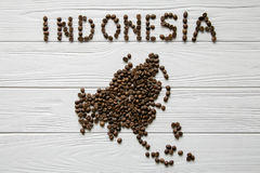 Map of the Indonesia made of roasted coffee beans laying on white wooden textured background. Space for text Royalty Free Stock Photos