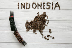 Map of the Indonesia made of roasted coffee beans laying on white wooden textured background with toy train. Space for text Royalty Free Stock Photo