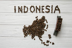 Map of the Indonesia made of roasted coffee beans laying on white wooden textured background with toy train. Space for text Royalty Free Stock Photography