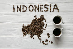 Map of the Indonesia made of roasted coffee beans laying on white wooden textured background with two cups of coffee stock photo
