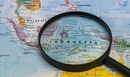 Map of Indonesia through magnifying glass on a world map. Indonesia map through magnifying glass on a world map royalty free stock image