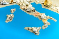 Map of Italy and islands in the Mediterranean from sand. On top are seashells stock photos