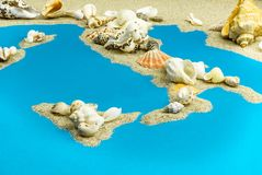 Map of Italy and islands in the Mediterranean from sand. On top are seashells royalty free stock image