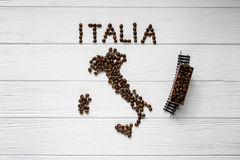 Map of the Italy made of roasted coffee beans laying on white wooden textured background with toy train Royalty Free Stock Photography