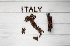 Map of the Italy made of roasted coffee beans laying on white wooden textured background with toy train Stock Photo