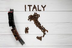 Map of the Italy made of roasted coffee beans laying on white wooden textured background with toy train Stock Image