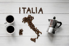 Map of the Italy made of roasted coffee beans laying on white wooden textured background with two cups and coffee maker Stock Images