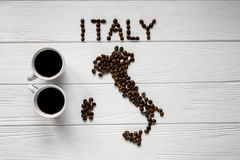 Map of the Italy made of roasted coffee beans laying on white wooden textured background with two cups of coffee Royalty Free Stock Image