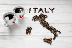 Map of the Italy made of roasted coffee beans laying on white wooden textured background with two cups of coffee. Space for text stock photography