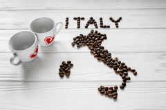Map of the Italy made of roasted coffee beans laying on white wooden textured background with two cups of coffee Stock Photo