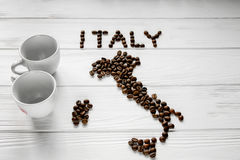 Map of the Italy made of roasted coffee beans laying on white wooden textured background with two cups Royalty Free Stock Image