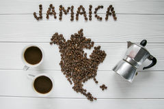 Map of the Jamaica made of roasted coffee beans laying on white wooden textured background with coffee maker and cups of coffee. And space for text Royalty Free Stock Photography