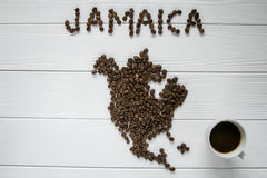 Map of the Jamaica made of roasted coffee beans laying on white wooden textured background with cup of coffee. And space for text Stock Photography