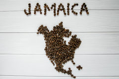 Map of the Jamaica made of roasted coffee beans laying on white wooden textured background. And space for text Stock Photos