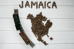 Map of the Jamaica made of roasted coffee beans laying on white wooden textured background with toy train. And space for text Royalty Free Stock Photo