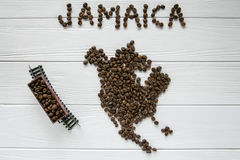 Map of the Jamaica made of roasted coffee beans laying on white wooden textured background with toy train. And space for text Royalty Free Stock Photos