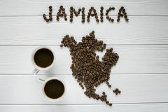 Map of the Jamaica made of roasted coffee beans laying on white wooden textured background with two cups of coffee. And space for text Stock Image