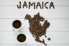 Map of the Jamaica made of roasted coffee beans laying on white wooden textured background with two cups of coffee. And space for text Royalty Free Stock Image