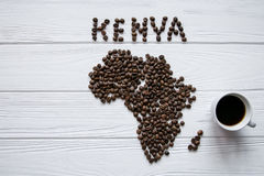Map of the Kenya made of roasted coffee beans laying on white wooden textured background with cup of coffee. And space for text Royalty Free Stock Images