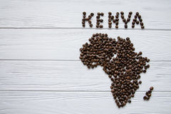 Map of the Kenya made of roasted coffee beans laying on white wooden textured background. And space for text Royalty Free Stock Images