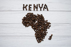 Map of the Kenya made of roasted coffee beans laying on white wooden textured background. And space for text Stock Image