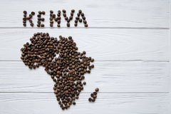 Map of the Kenya made of roasted coffee beans laying on white wooden textured background. And space for text Stock Photos