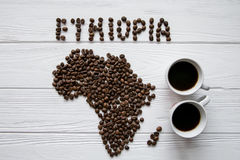 Map of the Kenya made of roasted coffee beans laying on white wooden textured background with two cups of coffee. And space for text Stock Photo