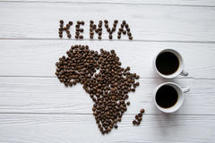 Map of the Kenya made of roasted coffee beans laying on white wooden textured background with two cups of coffee. And space for text Royalty Free Stock Images