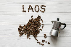 Map of the Laos made of roasted coffee beans laying on white wooden textured background with coffee maker. Space for text Royalty Free Stock Images